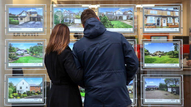 Couple looking at an estate agent's window © Getty images