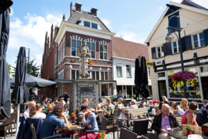 Arnhem, the Netherlands - August 8, 2013: People sitting on a terrace in the inner city of Arnhem. Around the square are several shops, the square is called Jansplaats. In the background a statue of Karel (1467-1538), Duke of Gelre and Count of Zutphen between 1492 and his death.